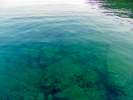 Transparent water surface through which it is seen. Top view of the sea, lake, river, pond. Natural blue - green beautiful background image. Stock Photo