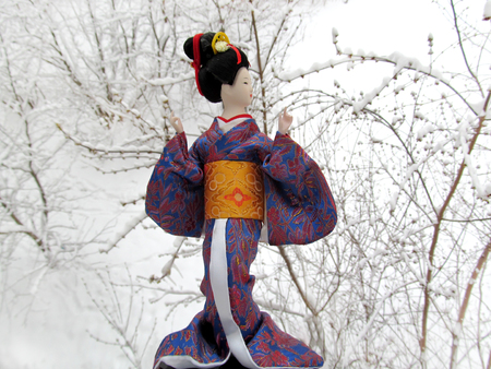Japanese geisha girl in a doll image. A beautiful woman in traditional kimono. Female gardener with white snow.