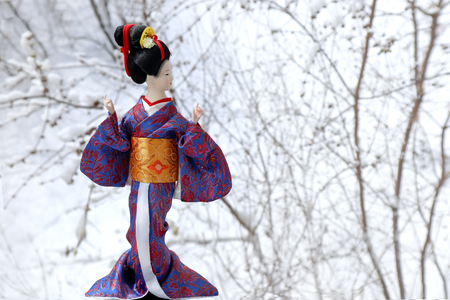 Japanese geisha girl in a doll image. A beautiful woman in traditional kimono. Female gardener with white snow. 写真素材