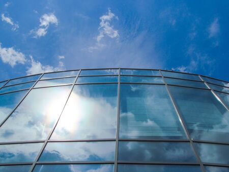 Modern glass building against blue sky background. Bottom view of the windows of the facade. Abstract fragment of contemporary architecture. Stok Fotoğraf
