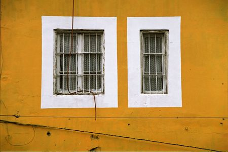 graphical: two white windows in the middle of a yellow wall
