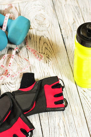 Sports accessories. Gloves, dumbbells, bottle, centimeter tape.