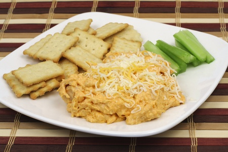 Appetizer buffalo chicken dip with crackers and celery