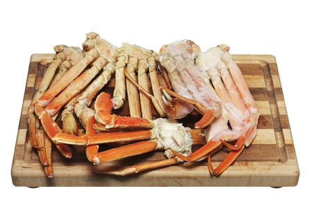 Crab legs on a cutting board isolated on white Stock Photo