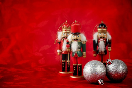 Three nutcrackers stand on red Christmas background with ornaments photo