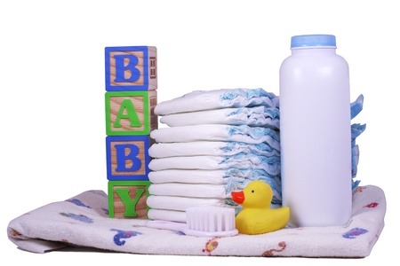 Items for a new baby, diapers, powder, receiving blanket, rubber duck, and brush isolated on white photo