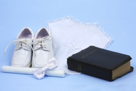 Religious baptism items, candle, shoes, bow tie, and bible on blue background