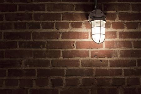 Creepy light bulb on textured red brick wall photo