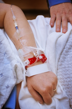 patients: Married woman with infusion in arm in hospital with husband  Stock Photo