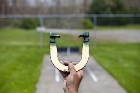 Player lines up to pitch a horseshoe in an outdoor court, hand and horseshoe in focus photo