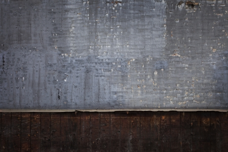 Brick wall with peeling gray paint with wooden panels underneath grunge background photo