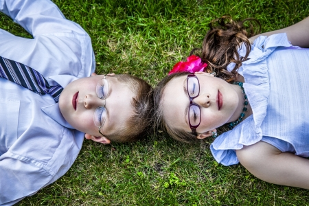Young brother and sister lay down in the grass dressed up close their eyes relaxing in the grass outside photo