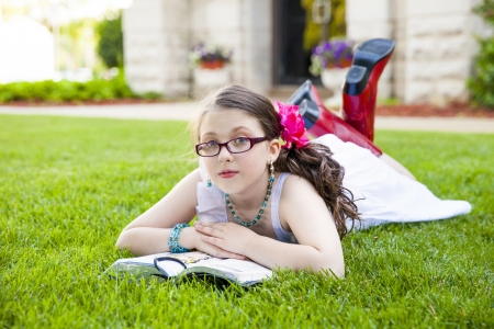 Beautiful young hispanic girl in glasses, white dress, and red boots, reads her book outside on the grass photo