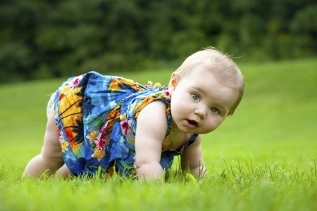 baby crawling: A Japanese American toddler girl learns to crawl outside