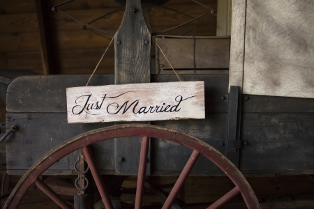 annoucement: A just married sign hangs on the side of a vintage wagon