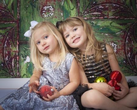 Twee zussen poseren voor foto's met Kerst ornamenten en decoraties Stockfoto