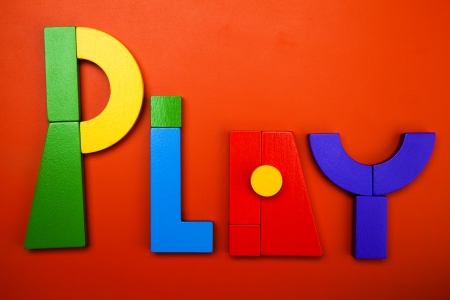 color tangram: the word play written in blocks on red
