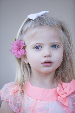blue eyed: Blue eyed young caucasian girl with blond hair looks seriously at the camera Stock Photo