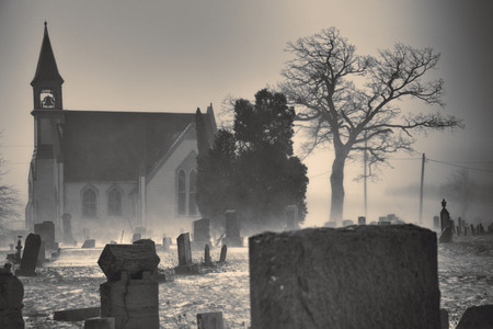 gravestones: A Cumberland, Maryland church sits behind a graveyard with fog creating an eerie, spooky feeling. Monochromatic image with focus on the gravestones.