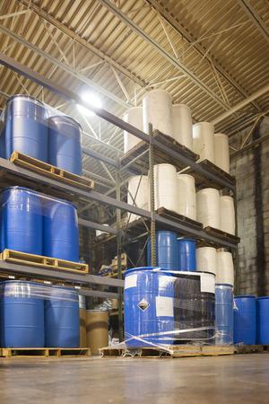 Tambores de 55 galones se apilan en paletas en un almacén químico industrial. Una etiqueta corrosiva es visible en un tambor. Foto de archivo