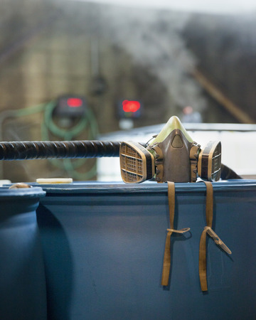 respirator: A respirator, chemical safety equipment, sits on a 55 gallon drum in a chemical plant. Gasses emit from containers in the background. Corrosive industrial environment.