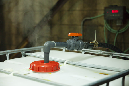 corrosive: A wand pump leads into a mixing tank in an industrial chemical plant. Gas from hydrochloric acid emits from the container. Corrosive environment