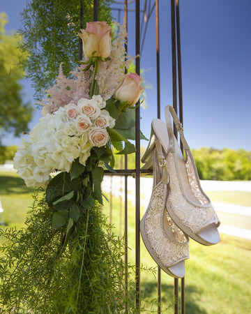 wedding photography: Wedding photography brides shoes hanging outside by beautifully styled flower arrangement outside. Preceremony getting ready image