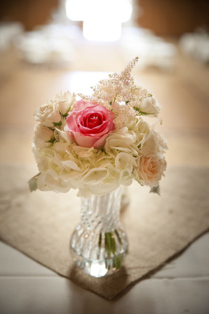 Wedding flowers on venue table centerpiece with pink roses and stock photo wedding flowers on venue table centerpiece with pink roses and white flowers in glass vase shallow depth of field mightylinksfo
