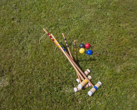 A croquet set. Four wooden mallets, four balls, two hoops on grass field