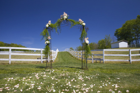 venue: Outdoor ceremony floral archway with petals in the grass. Farm venue set up for wedding day. Stock Photo