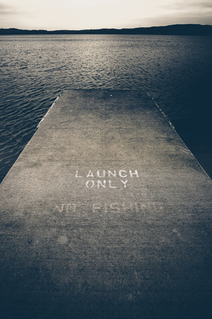 Looking down pier of boat launch on lake in winter. Words on pier say Boat Launch No Fishing. Black and whtie filtered style. Vertical.