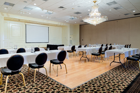 Empty hotel conference meeting or event room provides space for business meetings, conferences, speakers, or events. Tables and chairs set up to view projection screen.