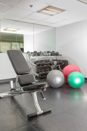 weight room: Fitness weight room dumbells, fitness balls, and weight bench in hotel fitness workout room