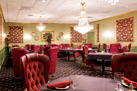 tablecloth: Elegant upscale hotel dining room area with red leather chairs, statues, and chandeliers.