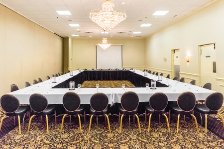 Hotel conference meeting room with tables and chairs set up facing each other. Projection screen is in back of room. Stock Photo