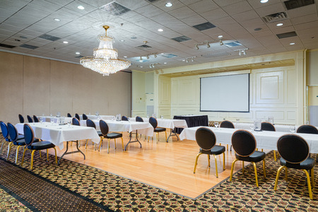 Empty hotel conference meeting room with chairs and tables set up before a white projection screen