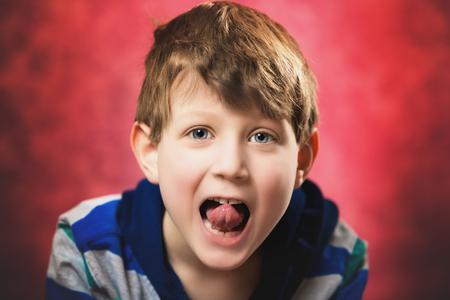 Een zeven jaar oude blanke jongen steekt speels zijn tong uit naar de camera. Rode achtergrond. Stockfoto