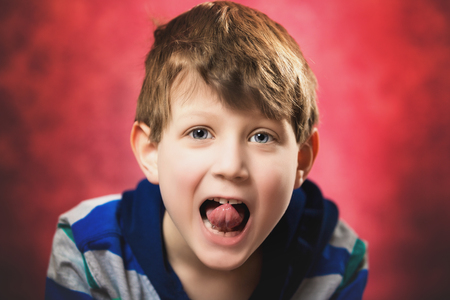 One seven year old caucasian boy playfully sticks his tongue out at the camera. Red background.