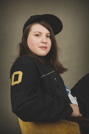 sits on a chair: One twelve year old caucasian girl sits in yellow chair wearing black outfit and hat.