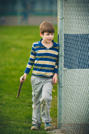 autistic: Autistic boy with stick wearing striped shirt. Outside next to fence.