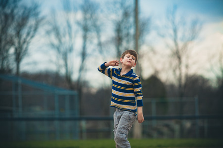 Caucasian autistic boy in striped shirt pretends to throw a ball outside Reklamní fotografie