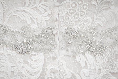 Close up of white wedding dress lace and fabric