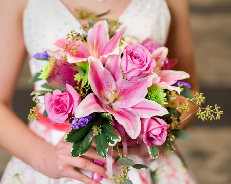 Teen girl holding pink rose and lily bouquet getting ready for prom.