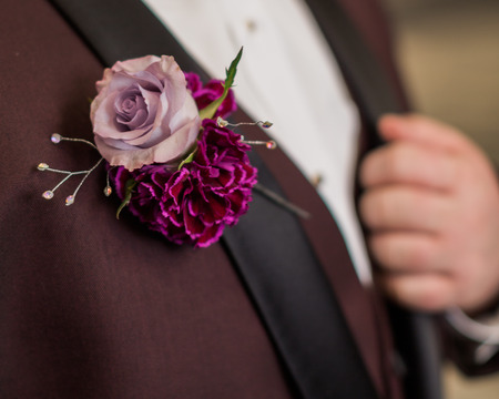 Detail of boutonniere. High school teen boy with pinned boutonniere on formal suit. Фото со стока