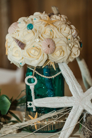 Cute, Fun, Handmade. Beach Themed Ocean Wedding Reception Decorations. Party Centerpiece with Floral Bouquet, Starfish, and Key