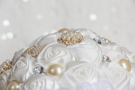 White shimmering wedding bridal bouquet with white roses and pearl details. Close up wedding detail photo.
