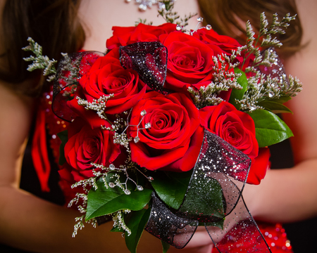 Close up of red rose prom bouquet with coordinating ribbon.