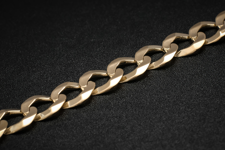 Close up of the links of a mens Cuban link solid gold bracelet on black textured background