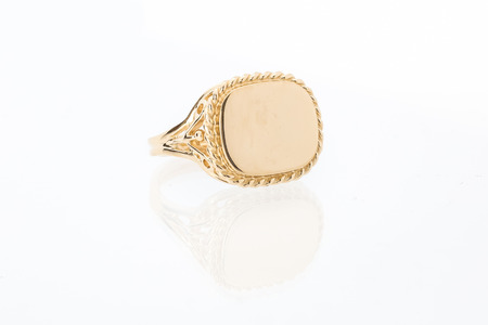 One mens gold bezel ring with plain shiny flat golden surface on white background with reflection