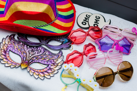 Photo booth props including funny glasses, masks, signs, and colorful hats. Фото со стока